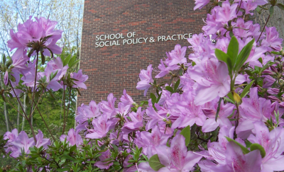 School of Social Policy & Practice sign on the Caster Building seen with pink azaleas.