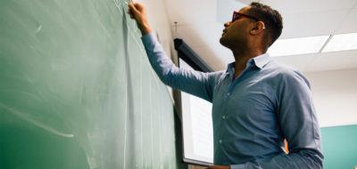 Ezekiel Dixon-Roman teaching a course, writing on a chalkboard.