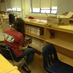 A Community Teamworks volunteer helps to organize books on newly built shelves.
