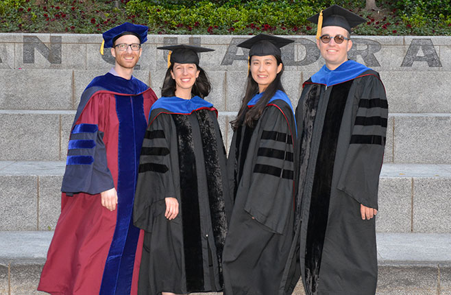 PhD graduates pose for a photo