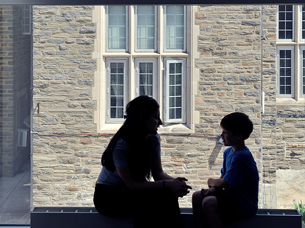 Social worker and child sit in front of window