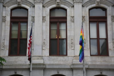 U.S. flag and the new LGBTQ flag, side by side in front of Philadelphia CIty Hall