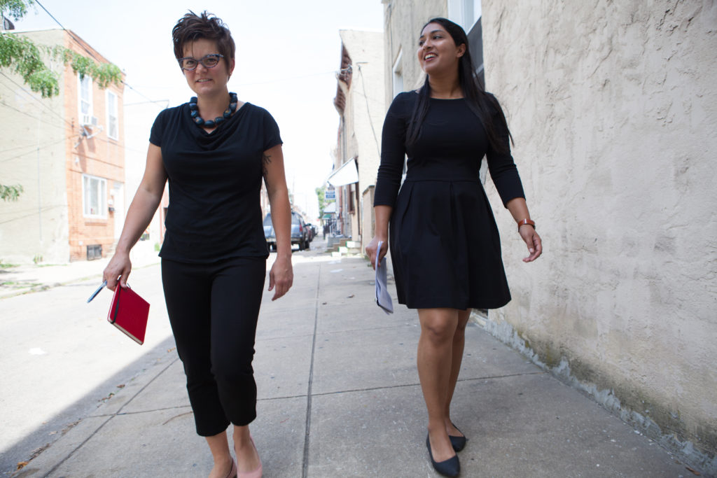 Amy Castro Baker and Henisha Patel walking along a sidewalk in South Philadelphia