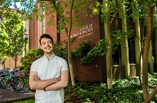 Joshua Jordan in front of the School of Social Policy & Practice