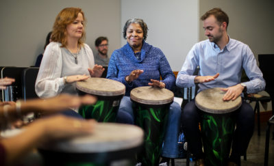"Mary Javian, chair of career studies at the Curtis Institute, Tempy Small, a program participant, and Adam Pangburn, coordinator of community performance at Curtis, participated in a drum circle at a ""Creative Expression through Music"" session. Nick DiBerardino (not pictured) lead the classes, which were coordinated by Penn graduate students Sarah Bujno and Matt Volpe (in the background)."