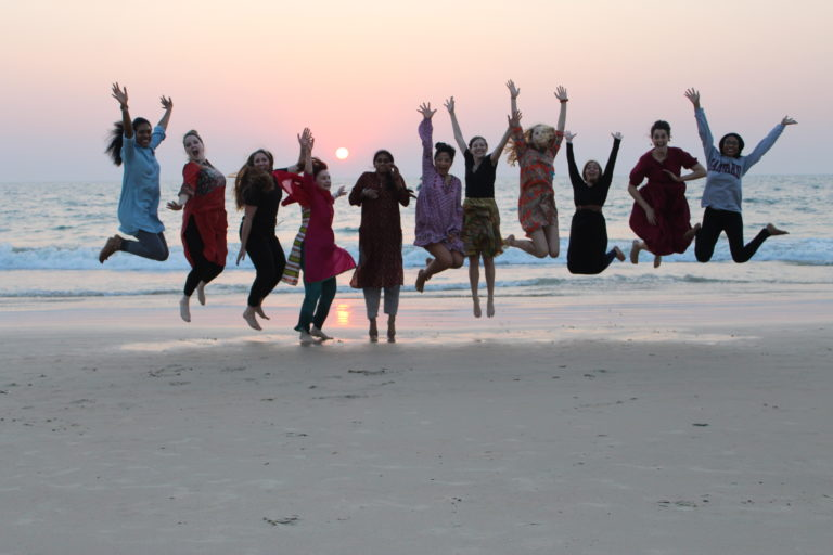 Students jump on a beach