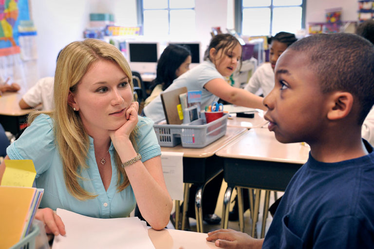 Student listens to child in classroom
