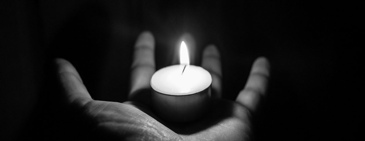 tea light reflecting on hand in the dark