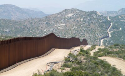 U.S./Mexico border with wall in foreground and mountains behind